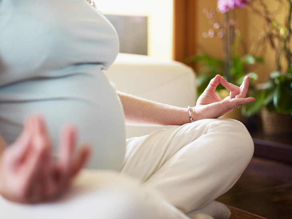 pregnant woman doing yoga at home